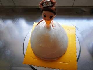 萌翻少女心-芭比蛋糕,抹面后再放芭比,用保鲜膜把芭比腰部以下包起来插入蛋糕体内,不要插到太靠下,到臀部就可以了,否则做好的娃娃看上去没有腰。
