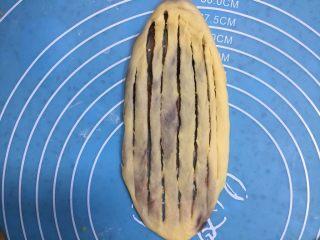 扭扭层层豆沙面包,用擀面杖轻轻的擀成薄薄的椭圆形,再用切刀划口,除两头不划断中间刀口划断