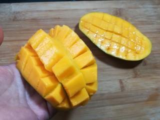 芒果酸奶杯,手在芒果皮位置往上一顶,芒果就会成图中的状态。这时就可以很方便的切下芒果的小块。