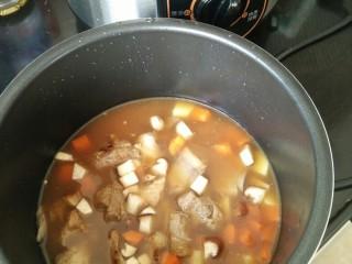 排骨土豆焖饭,倒入排骨以及汤汁,如果水不够就再加适量水,水位跟平时煮饭一样。