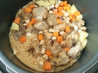 排骨土豆焖饭,开盖,放入葱花,搅拌均匀。