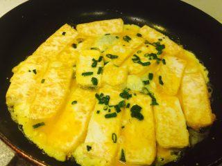 香煎豆腐,豆腐两面煎金黄后,倒入剩余的蛋液,慢慢煎至蛋液成熟即可。