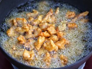 菠萝咕咾肉,再次升高锅中油温,将肉块复炸一遍,待肉块金黄酥脆后捞出控油