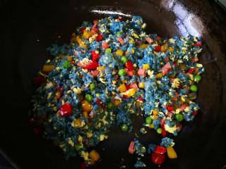 蝶豆花五彩炒饭,加入鸡蛋、米饭和少许盐。用勺子背轻拍米饭,把米饭炒散。略加煸炒就可以出锅了,按自己口味还可以加入孜然粉。