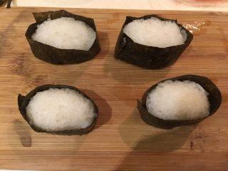 握寿司套餐,将海苔剪成2cm宽,将米饭团圈起