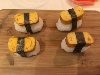 握寿司套餐,将海苔剪成1cm宽,将寿司卷起来
