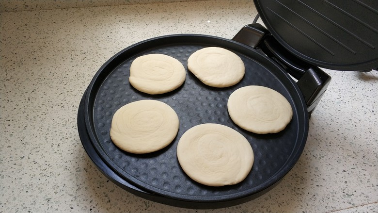 肉夹馍,擀好的面饼码在电饼铛上。