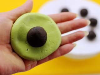 清新碧绿的青叶汁黑芝麻豆沙青团,把面团用手摁扁放入豆沙黑芝麻馅料