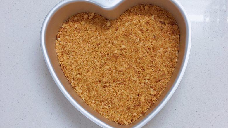 春日樱花慕斯,把饼干碎和融化的黄油混合,铺在模具底部,用勺子压平。
