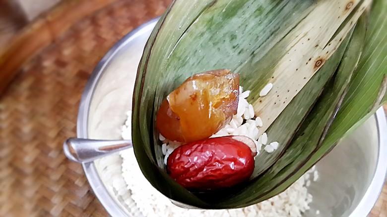 古法特制、天然植物碱水粽,用事先处理好的粽叶开始裹粽。
