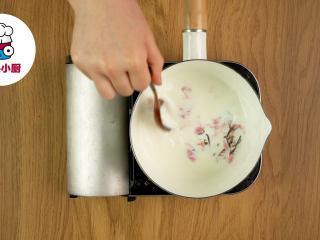 樱花豆乳慕斯杯!,盐渍樱花用温水泡开(去掉过多的盐味),捞出放入奶锅中,倒入牛奶120ml,开小火边搅拌边煮至冒小泡,关火,滤出樱花不用