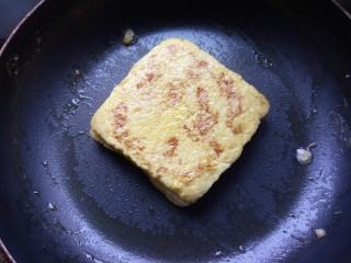 火腿西多士,黄油融化后放入西多士,小火进行煎制,每一面都煎金黄。