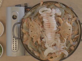 海鲜大锅,最后把切好的鱿鱼放在中间,盖上锅盖煮8到15分钟。