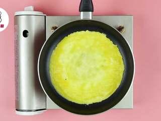 网红波点蛋包饭,平底锅刷油,开小火烧热,倒入蛋液摊开,待其凝固立刻关火