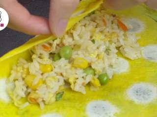 网红波点蛋包饭,将煎好的蛋皮翻面,中间铺入炒饭,左右对折包起