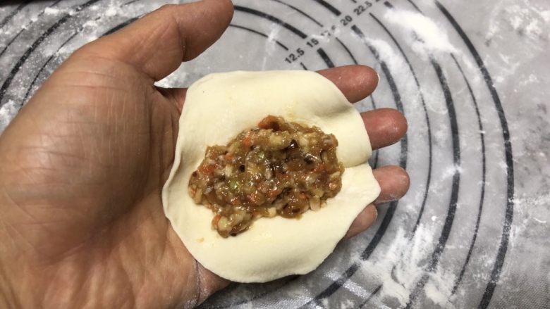 美味虾蛋报饺,松弛好的面团取出,揉匀之后搓成长条,再分成大小相等的剂子,擀圆之后成为饺子皮。 取一个饺子皮,放入一勺肉馅