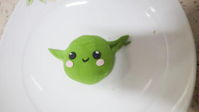 丑萌的青团,我们绿的不一样,将面团按扁一点就是脸。用竹炭粉做成眼睛,用一点点水安上耳朵。粉色的是腮红,还有嘴巴,因为很小所以你可以用牙签帮助黏贴。