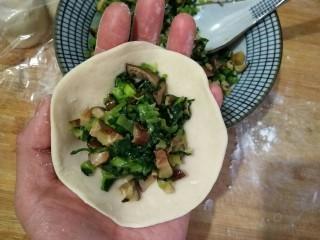 香菇油菜包,将面剂擀成中间后边缘薄的面皮,在中间填入适量的馅料。