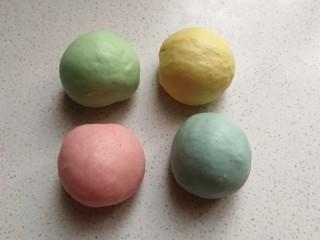 春之色~彩虹面包卷,四份小面团中分别加入四种颜色的食用色素,揉均匀后并滚圆,再摆入烤盘中盖上保鲜膜放温暖处发酵