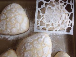 什香草土豆面包,发酵好的面包胚上盖一张图案纸,撒上面粉。