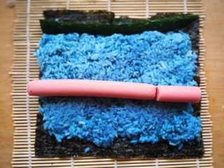花朵寿司【蓝色系】,中间摆火腿肠,前端摆黄瓜条。火腿肠一根不够长再加上一段。