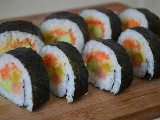 寿司,准备一个湿布,刀每切一下最好擦干净再切,不然会粘米粒,第二刀会很粘。依次切好。