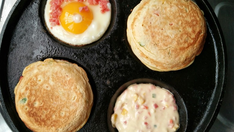 什锦蛋黄堡,另一种方法,也可以先煎鸡蛋,再舀面糊,在面糊未干前将煎好的鸡蛋放上,这样鸡蛋的两面都能和面糊粘合在一起了。(只是这种做法如果要刷酱料或夹菜时需要将蛋堡再用刀从中间片开)
