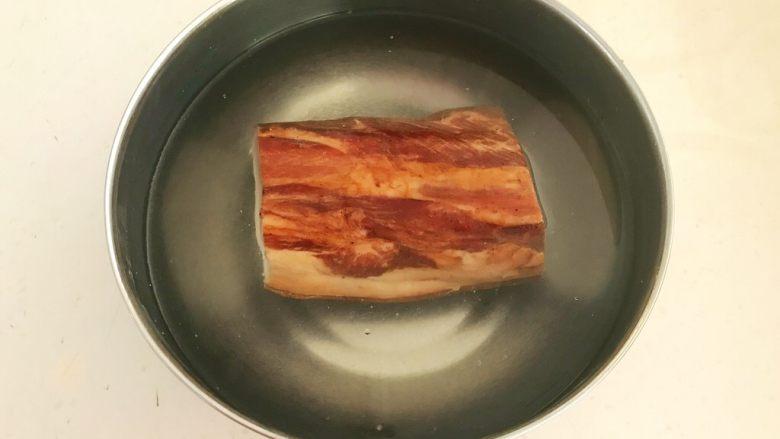 苦菊卷黑椒腊肉,把腊肉清洗干净,放入温水中浸泡2小时,