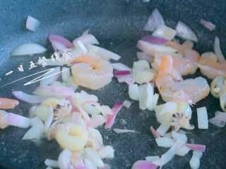 南瓜海鲜意面,锅中倒少许油,将洋葱炒出香味,放入虾仁、墨鱼仔,炒2分钟。 >>西餐中洋葱经常看到,在这里起到去腥增香作用。