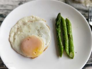 养颜营养早餐,煎好的鸡蛋装入盘子,芦笋装盘撒上胡椒粉