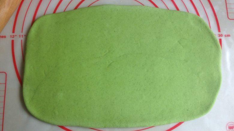 菠菜馒头,发酵好的面团揉几分钟排排气,用擀面棍将面团擀成长方形。