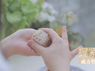 春の饭团的2+1种有爱做法「厨娘物语」,取30g米饭握紧成一个小正方形,放上1块煎好的午餐肉,包入海苔片。