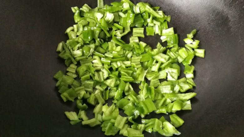 青椒拌皮蛋,锅烧热,无需放油,先倒入青椒碎煸炒一会儿