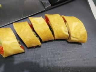 香椿蔬菜蛋皮卷,把卷好的蔬菜卷切小段。