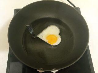 黑椒腊肠炒意面,炒锅烧热后加入大豆色拉油,心形模具放在锅里,打入鸡蛋液,煎成一个心形流心蛋