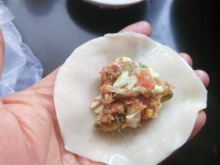 槐花馅饺子,饺子皮的边缘抹上清水,放适量的肉馅。