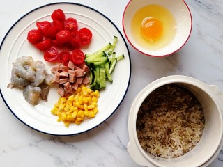 番茄虾仁蔬菜炒饭,准备好食材:鲜虾去壳去虾线,小番茄去皮对半切,香肠切丁,黄瓜切丝,甜玉米粒煮熟