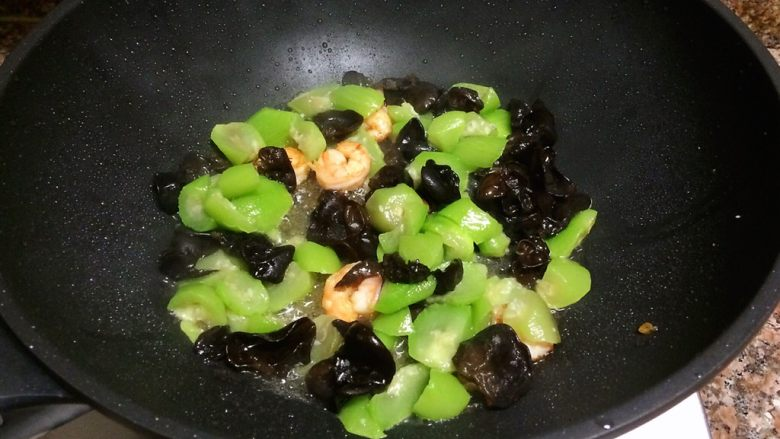 丝瓜虾仁跑蛋,放入丝瓜和木耳翻炒30秒。
