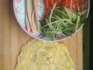 简单寿司,将鸡蛋饼火腿切成条,将黄瓜胡萝卜切成丝