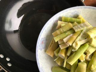 青椒油焖野笋,待锅内油七分热时,下野笋