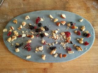 星空贝果(无黄油中式改良版),将切碎的坚果均匀撒在椭圆面片的表面。