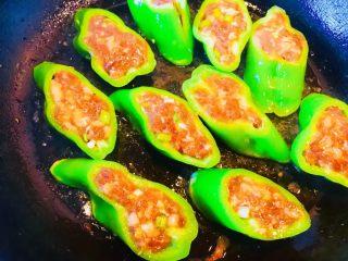 青椒酿肉,接着点火 把平底锅烧热 加少许色拉油 小火儿油温不要太高 放入青椒段把底部煎黄翻面