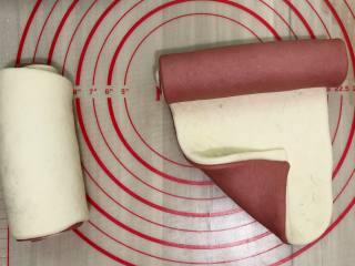 双色馒头,我把两个颜色一分为二,一个用红色的面皮在下,一个用白色面皮在下,这样两个卷出来的花色就不一样了,这个可按个人喜好,将两块面团重叠起来,用擀面杖轻轻按压,擀平,使两块面皮完全重叠。在重叠的面皮上抹上一点点水,尽量的抹均匀一点,这一步是不可以忽略的