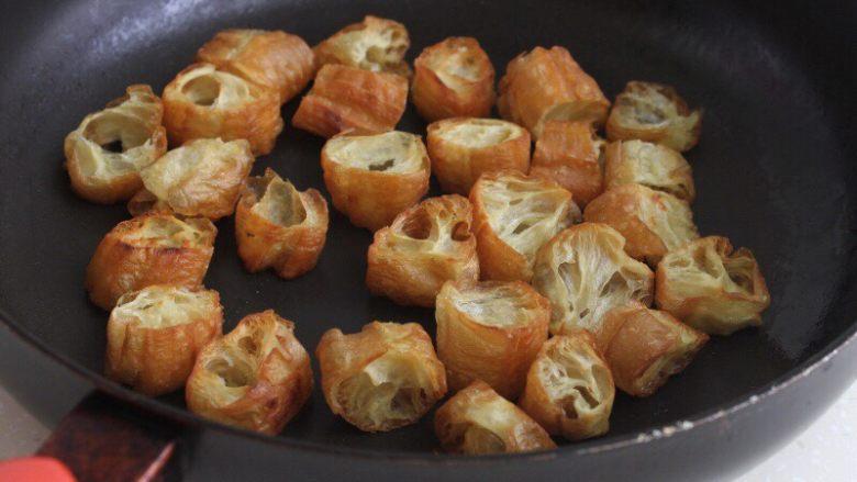 油条韭黄炒墨鱼,6.油条剪成小段,干煸至焦脆,盛到碗里 。