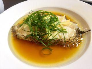 清蒸鳕鱼,葱花放在鱼肉上,热油浇入葱花上
