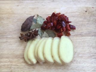 笋干红烧肘花肉,姜切片,草果用刀拍裂,准备好香叶和八角,干辣椒提前20分钟泡软,用厨房用纸吸干水分。