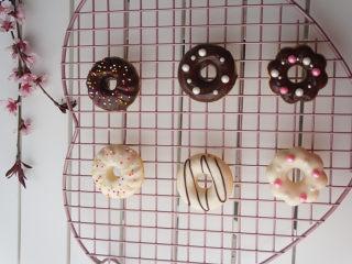 甜甜圈,甜甜圈一面蘸好巧克力液,装饰好糖珠就基本大功告成了。等到巧克力液凝固了就可以开吃了。