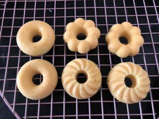 甜甜圈,烘烤结束后将甜甜圈放在晾网晾凉,这时可以准备一会要用的巧克力币和糖珠。