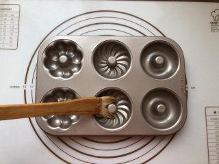 甜甜圈,黄油放到微波炉融化后均匀把模具刷一遍,这时可以预热烤箱了,温度设定为160度