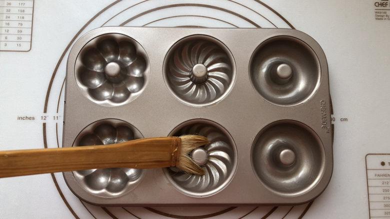 甜甜圈,<a style='color:red;display:inline-block;' href='/shicai/ 887'>黄油</a>放到微波炉融化后均匀把模具刷一遍,这时可以预热烤箱了,温度设定为160度
